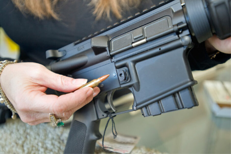 A California gun shop employee demonstrates how the 10-round magazine can be removed from a Stag Arms AR-15 type rifle using the tip of a bullet to depress the bullet button. It's one of the features that has made the rifle California legal. © Jebb Harris/ZUMA Press/Corbis