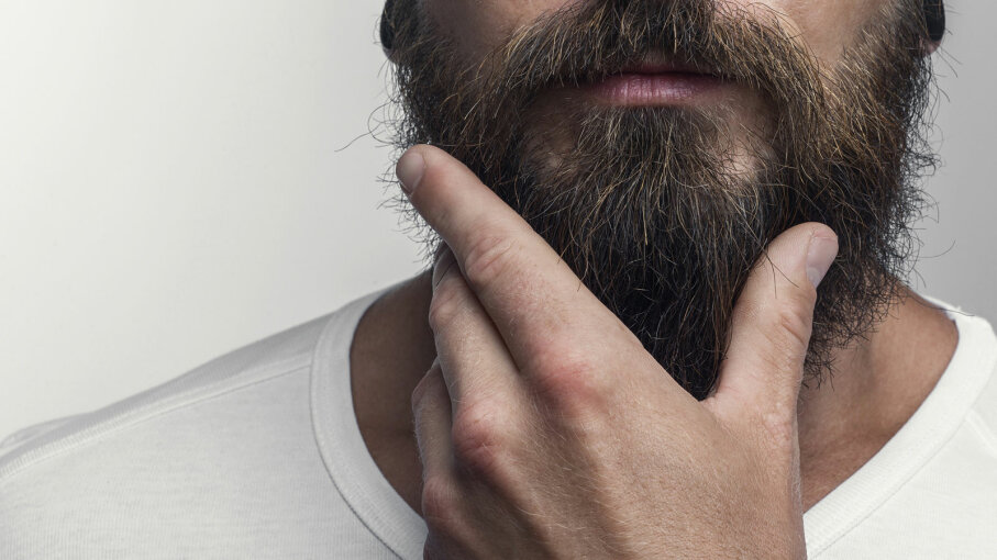 man stroking beard
