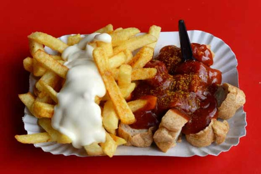 A traditional German currywurst, accompanied by french fries with mayonnaise, is served on a paper plate in the Prenzlauer Berg district of Berlin. © Jens Kalaene/dpa/Corbis