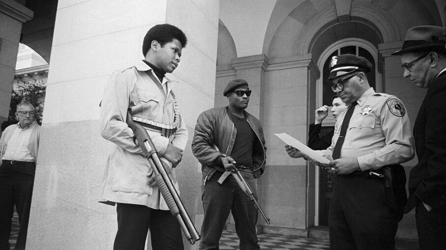 Two Black Panthers are met on the steps of the State Capitol in Sacramento by Police Lt. Ernest Holloway. Holloway told them they could keep their weapons if they did not disturb the peace. Earlier, party members had invaded the Assembly chambers and had their guns taken away. Bettmann/Getty Images