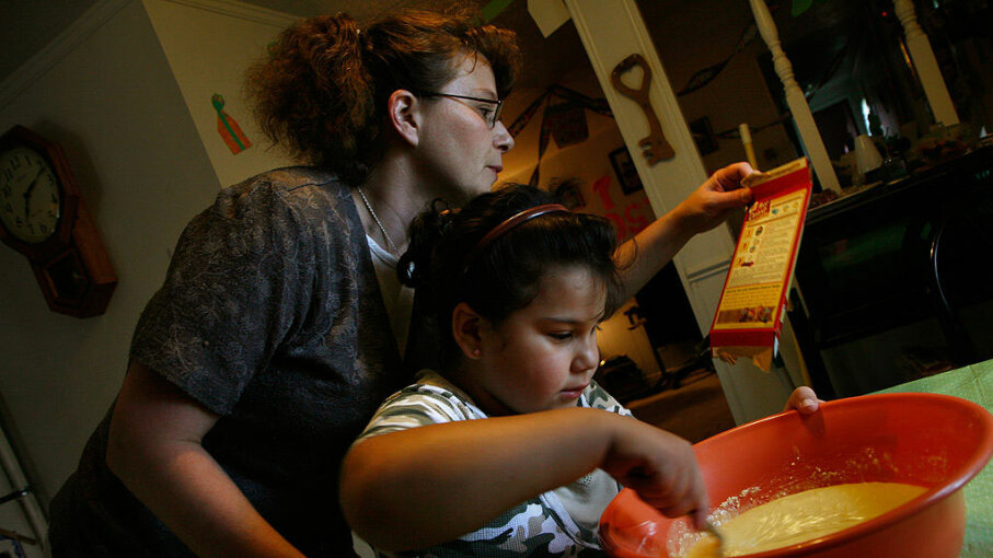 Christina Hall looks over the instructions on the back of the cake mix box, as her daughter Rosita Navarro, 7, stirs the batter for the young girl's birthday cake at their home in Alexandria, Virginia. Nikki Kahn/The Washington Post/Getty Images