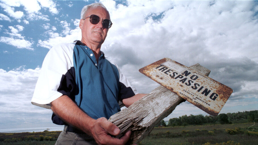 "Lynn Philip Hodgson, author of the book ""Inside – Camp X,"" holds an old sign from Camp X on the grounds of the former spy training school. Paul Irish/Toronto Star via Getty Images"
