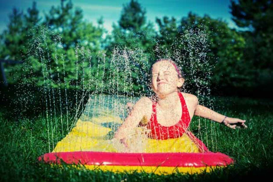 A girl enjoys the Slip 'N Slide on a sunny day. This is one toy best left to children -- unles you want to make one with an extremely long slide. Daniel Haug/Flckr/Getty Images