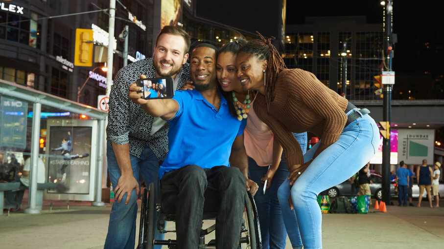 man in wheelchair with friends taking selfie