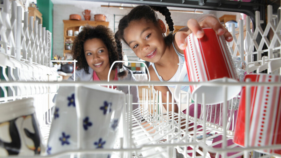 mother and daughter stacking dishwasher