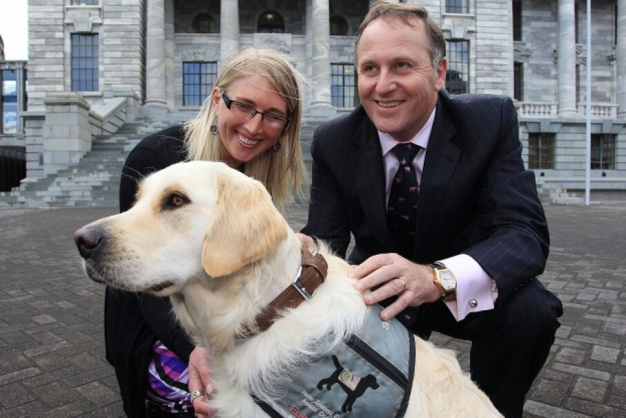 Epilepsy assist dog Roxy and her owner Kate Hendra pose with New Zealand Prime Minister John Key in October 2012. © Hagen Hopkins / Stringer/Getty Images
