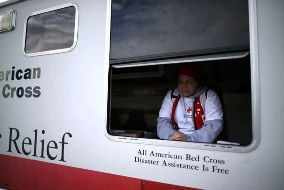 Red Cross worker Barbara Noble waits to give out free coffee to victims of Superstorm Sandy. If you donate to a well-known charity, you won't risk having your money go to fraudsters. Mark Wilson/Getty Images