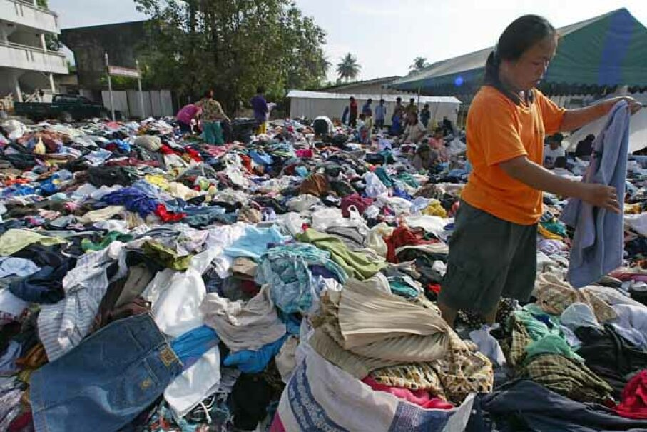 A woman picks through a mountain of used clothes at a donation center in southern Thailand, after the massive 2004 tsunami. PORNCHAI KITTIWONGSAKUL/AFP/Getty Images