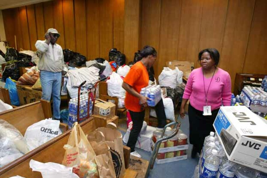 A Rainbow/PUSH worker (right) assists with organizing donated items to be shipped to Haiti in the aftermath of the earthquake. Experts say mixed donations like this are not the best way to help disaster victims. Tim Boyle/ Getty Images
