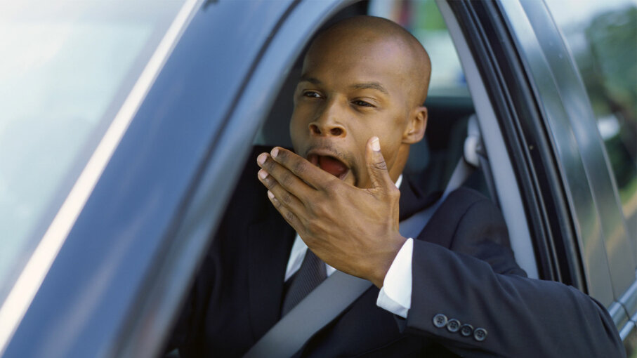 man yawning in car
