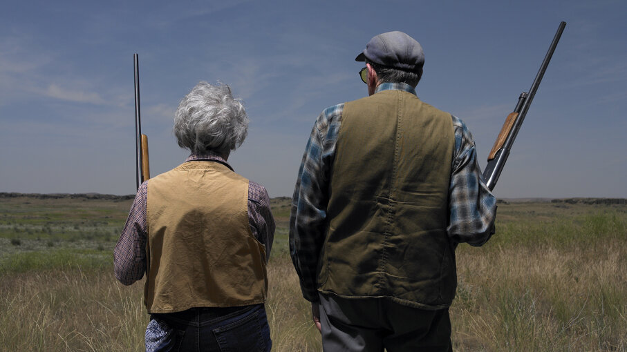Elderly couple, each with shotgun