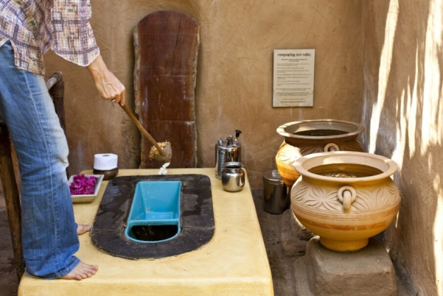 Use of a composting toilet is demonstrated at a yoga retreat in Goa, India in February 2012. Pots with material to cover waste and aid in decomposition are kept next to the latrine. © EyesWideOpen/Getty Images