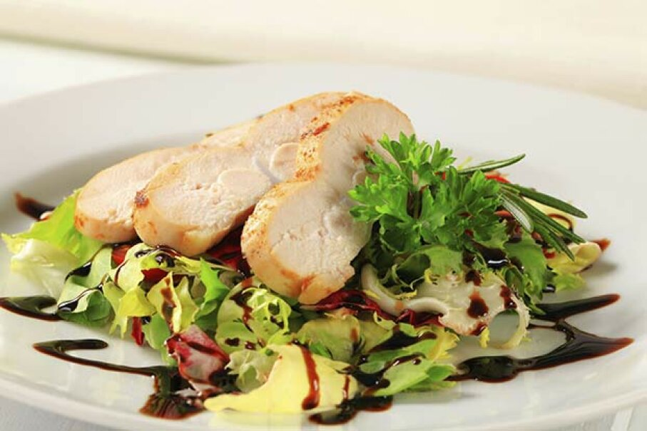 Though it's been prettified atop this salad, the boneless, skinless chicken breast usually tastes bland. vikif/iStock/Thinkstock