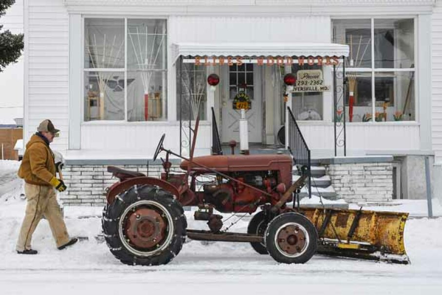 Monty Bussard walks back to his 1947 Farmall Model A tractor, after shoveling a sidewalk following a 2014 snowstorm in Myersville, Md. The tractor is one machine that revolutionized farming. Ricky Carioti/The Washington Post via Getty Images