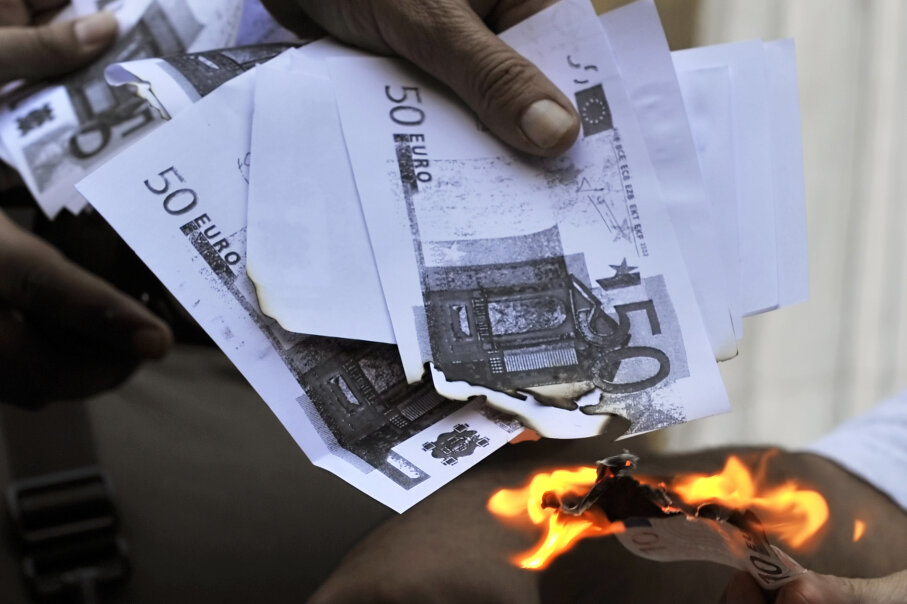 A protester sets fire to copies of euros in Greece in 2011. LOUISA GOULIAMAKI/AFP/Getty Images