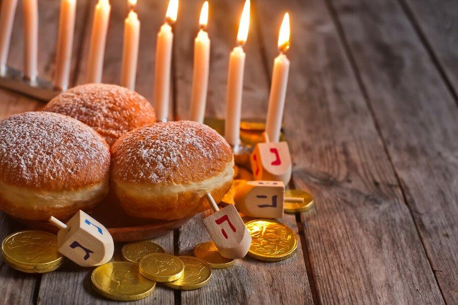 The eight-night celebration of Hanukkah includes symbols like the hanukkiah, doughnuts and dreidels. Karaidel/iStock/Thinkstock