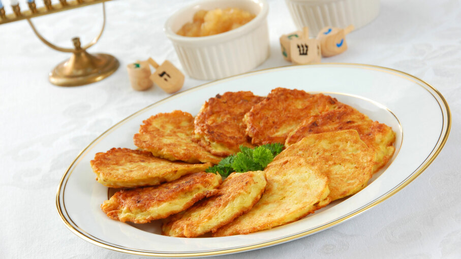 Latkes on a plate with dipping sauce on the side