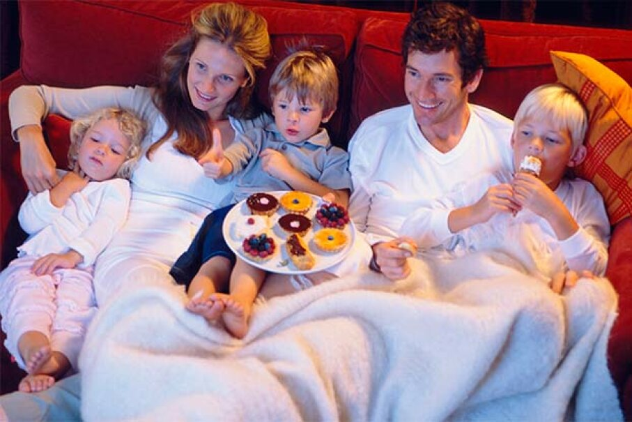 Snacking in front of the TV is often learned from parents. Goodshot/Thinkstock