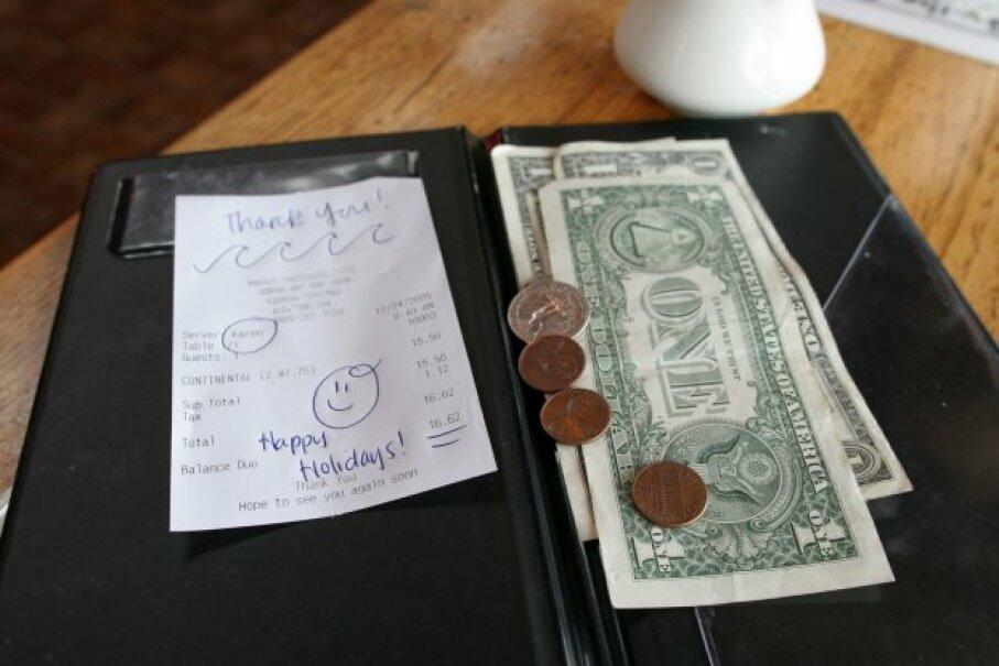 Restaurant check with cash in folder ©iStockphoto/Thinkstock