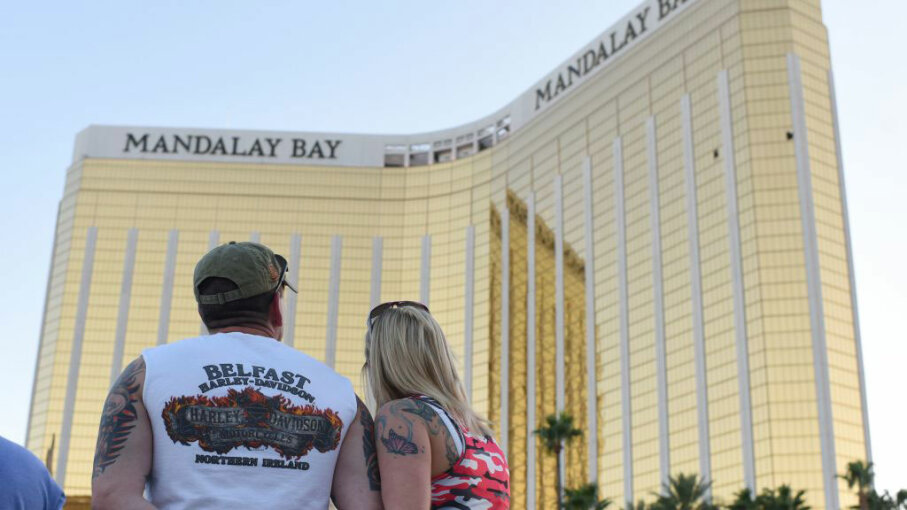 A couple stops on the Las Vegas Strip Oct. 4, 2017, to look up at the two broken windows in the Mandalay Bay hotel from which killer Stephen Paddock let loose the worst mass shooting in modern American history on Oct. 1, 2017. ROBYN BECK/AFP/Getty Images