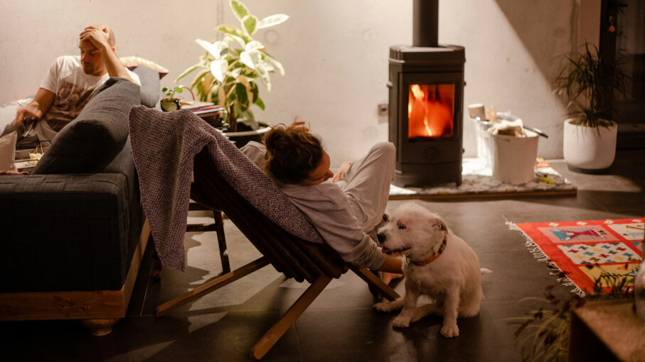 couple sitting by fire with dog