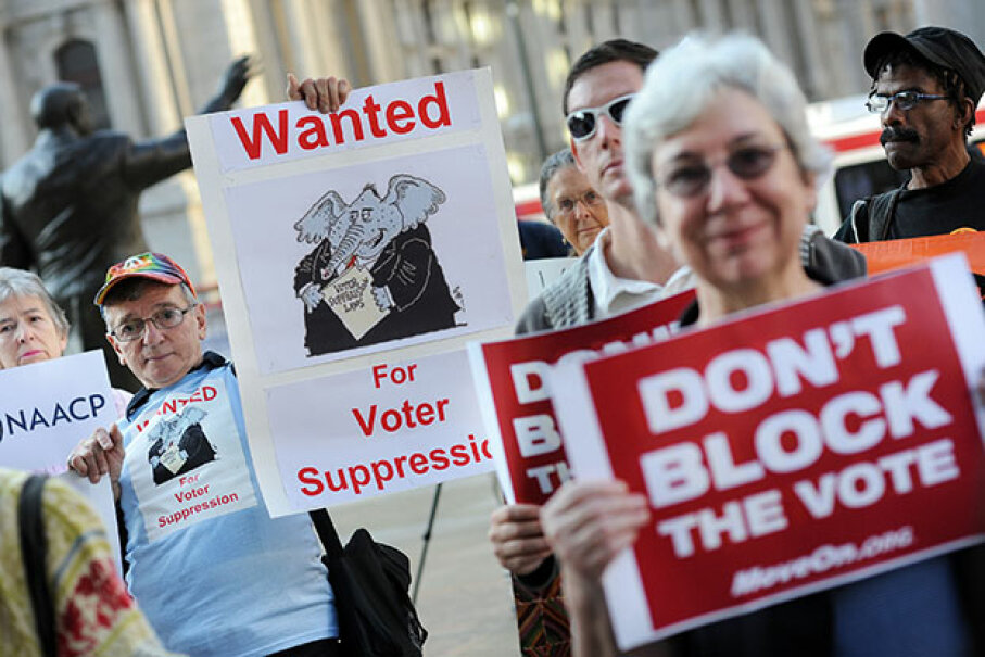 Demonstrators hold signs during a rally against voter ID laws, Sept. 13, 2012 in Philadelphia. William Thomas Cain/MCT via Getty Image