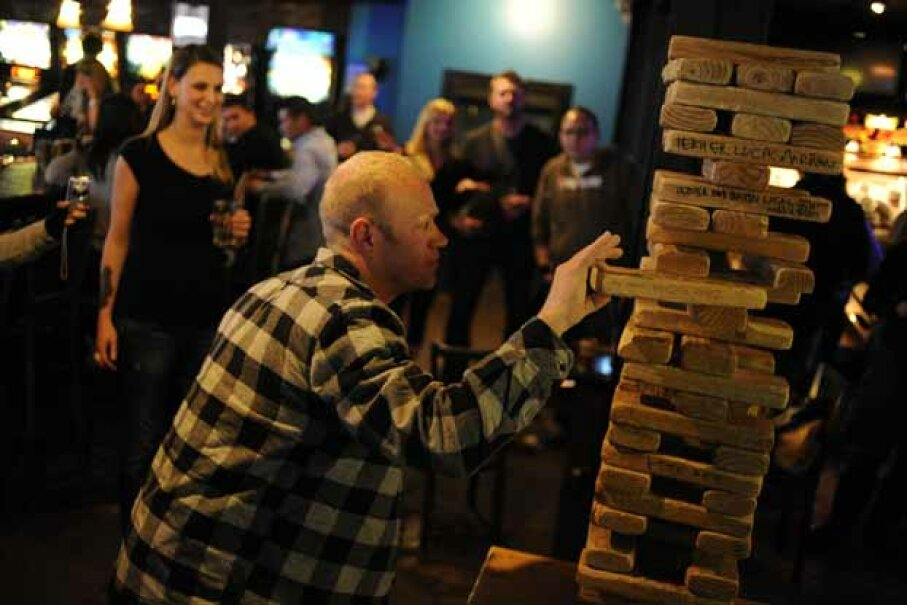 Troy Benson eases a block out an oversized Jenga game at a bar in Denver. AAron Ontiveroz/The Denver Post via Getty Images