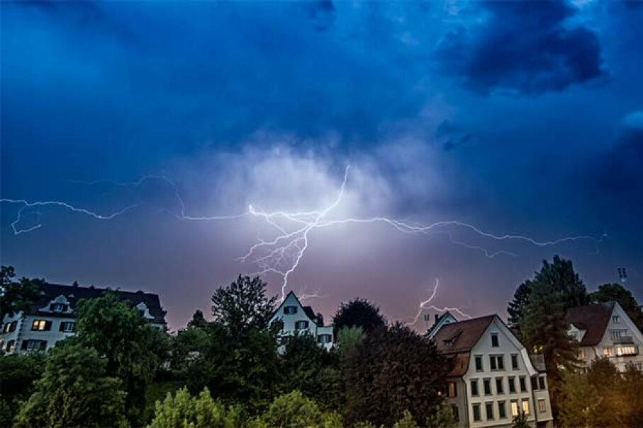 Even though being inside is far better than being outside during a lightning strike, you still want to keep away from things that conduct electricity indoors. Adrian Assalve/Getty Images