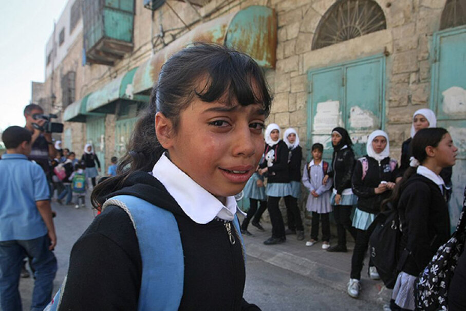 A Palestinian schoolgirl cries after Israeli forces use force to disperse a student protest in 2011. In 1983, both sides accused the other of deliberately trying to poison schoolchildren in the West Bank. The case was deemed one of mass hysteria. AZEM BADER/AFP/Getty Images
