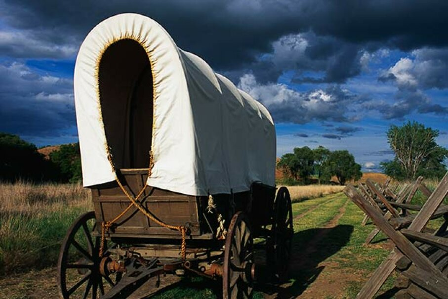A covered wagon along a wooden fence at the Whitman Mission National Historical Site in Washington state commemorates Marcus and Narcissa Whitman's role in establishing the Oregon Trail. © Connie Ricca/CORBIS