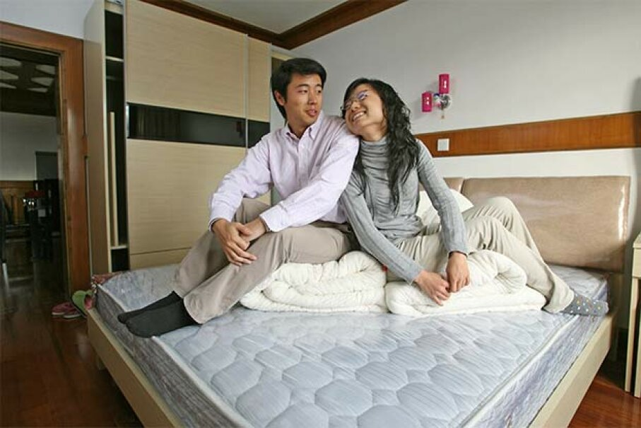 Lu Qin (left) and Li Chunqing pose on their bed in the new flat that they bought before their marriage in 2007 in Shanghai, China. Lucas Schifres/Getty Images