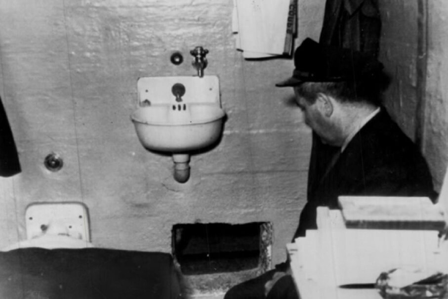 A prison guard kneels by the hole in Frank Morris' cell through which he and John and Clarence Anglin escaped. Prison officials report the hole was dug with broken spoons. Denver Post Rush Art (Photo By The Denver Post via Getty Images