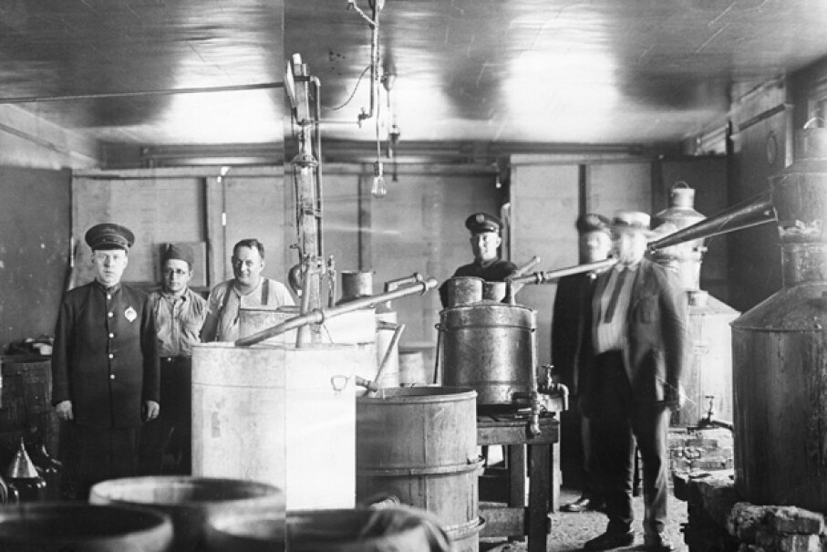 A view of the giant moonshine still taken by the police during a raid in Pittsburgh in 1922. Two of the alleged operators of the still are shown with their coats off. It was one of the largest stills taken since the advent of Prohibition. © Bettmann/CORBIS