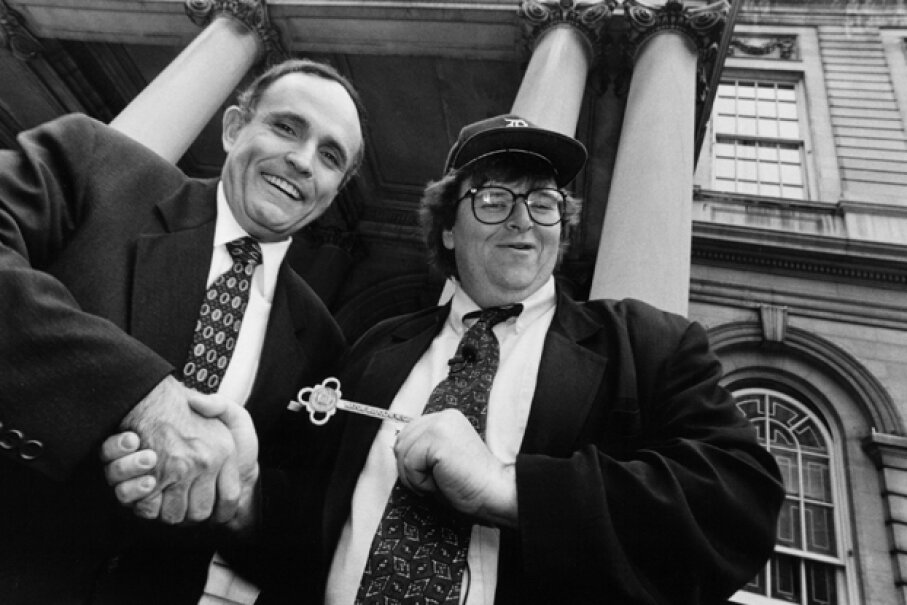 """New York City Mayor Rudolph Giuliani, left, gives the key to the city to filmmaker Michael Moore outside City Hall, during taping of an episode of Moore's NBC television series """"TV Nation"""" in May 1994. Catherine McGann/Getty Images"""