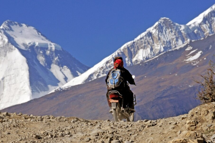 A motorcyclist traverses mountainous terrain in Nepal. The North Calcutta Disha Motorcycle Club holds the record for highest altitude reached by motorcycle. © Michel Gounot/Godong/Corbis