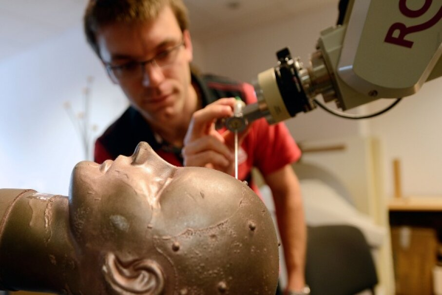 The ROSA robot, being checked here by a technician, is designed for helping surgeons perform brain procedures. © BORIS HORVAT/AFP/Getty Images)