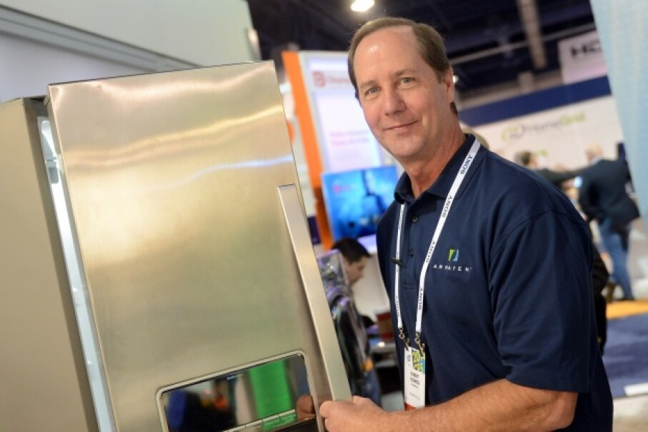 Employee Robert Kodweis from company Arrayent talks about the Internet of Things next to a refrigerator at the 2014 Consumer Electronics Show (CES) in Las Vegas. Arrayent makes an IoT platform. © Britta Pedersen/dpa/Corbis