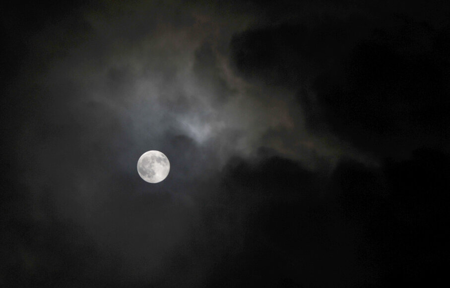 The moon appears from behind clouds.