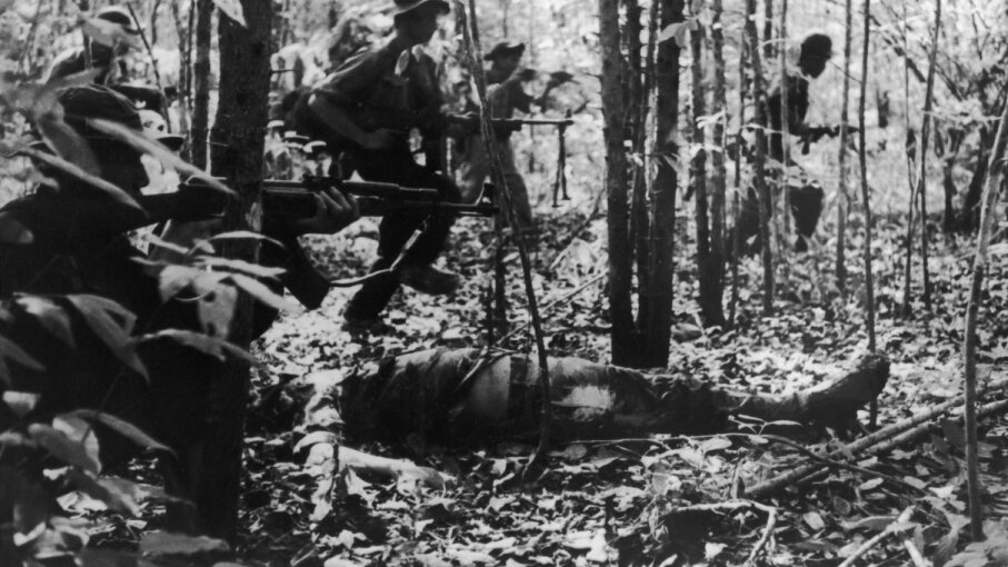 A Viet Cong detachment going into battle during the Vietnam War, January 1967. In the foreground is the body of a dead American soldier. Keystone/Hulton Archive/Getty Images