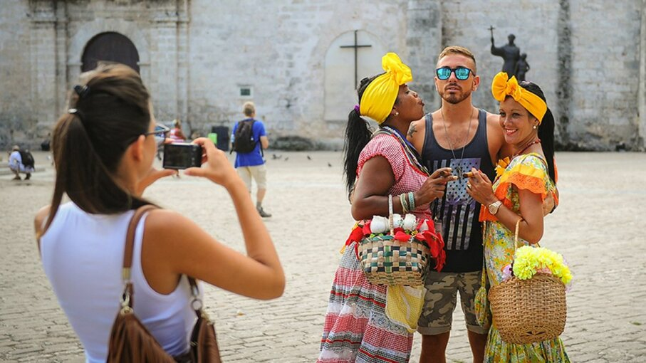 A U.S. tourist poses with women dressed in traditional clothing in the Old Town district of Havana, Cuba, in 2016. Yami Lage/AFP/Getty Images