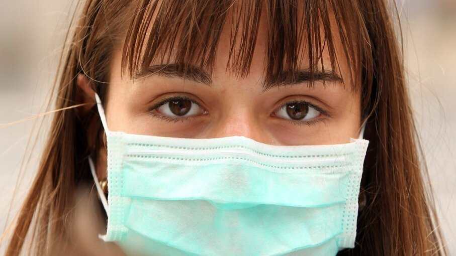 A woman wears a surgical mask to help prevent the spread of swine flu, an airborne infection. Oli Scarff/Getty Images