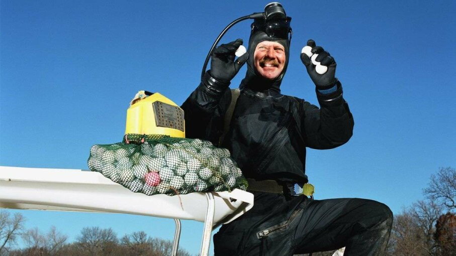 A golf ball diver hold up his hard-earned loot. Andrew Geiger/Getty