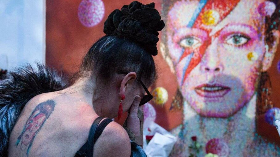 A woman with a tattoo of David Bowie cries in front of a mural of the British artist, painted by Australian street artist James Cochran, aka Jimmy C, following the January 11, 2016 announcement of Bowie's death. Justin Tallus/Getty Images