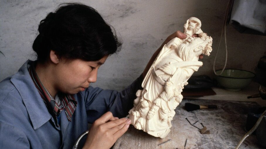 A Chinese woman creates a carving using elephant ivory. Dean Conger/Getty Images