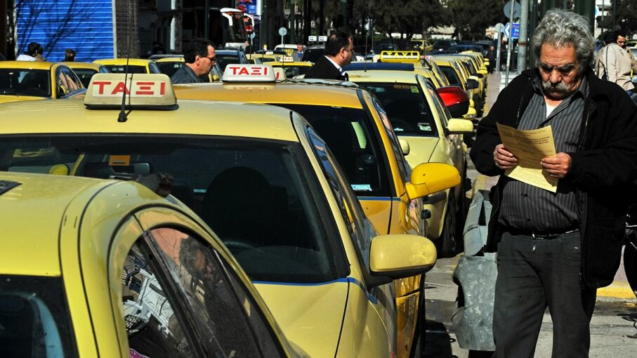 A taxi driver in Athens, Greece, reads his union's statement next to parked yellow cabs in 2010 during during a 24-hour strike to protest against fiscal reforms demanding the use of cash registers throughout the economy, and meters in taxis. Louisa Gouliamakia/AFP/Getty Images