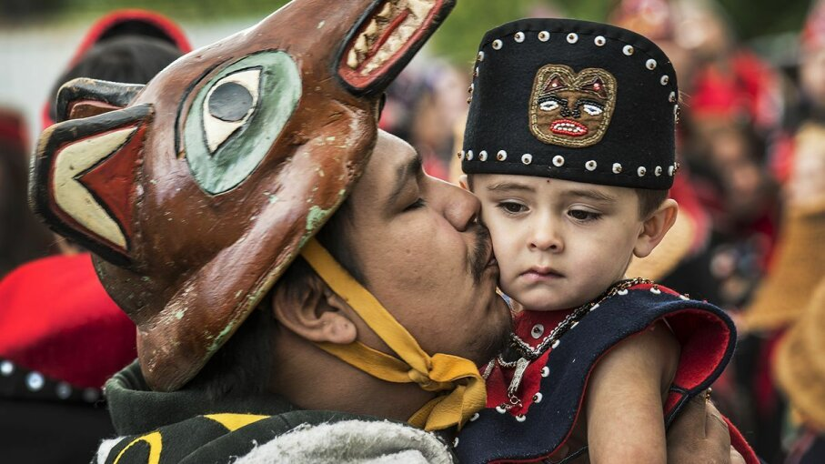 Tlingit tribe member J.J. Dewitt kisses his 2-year-old nephew Forrest Eide before they dance at the grand entrance of a 2014 Native American celebration in Juneau, Alaska. The Tlingit tribe has links to recently investigated archaeological sites. Linda Davidson/The Washington Post/Getty Images