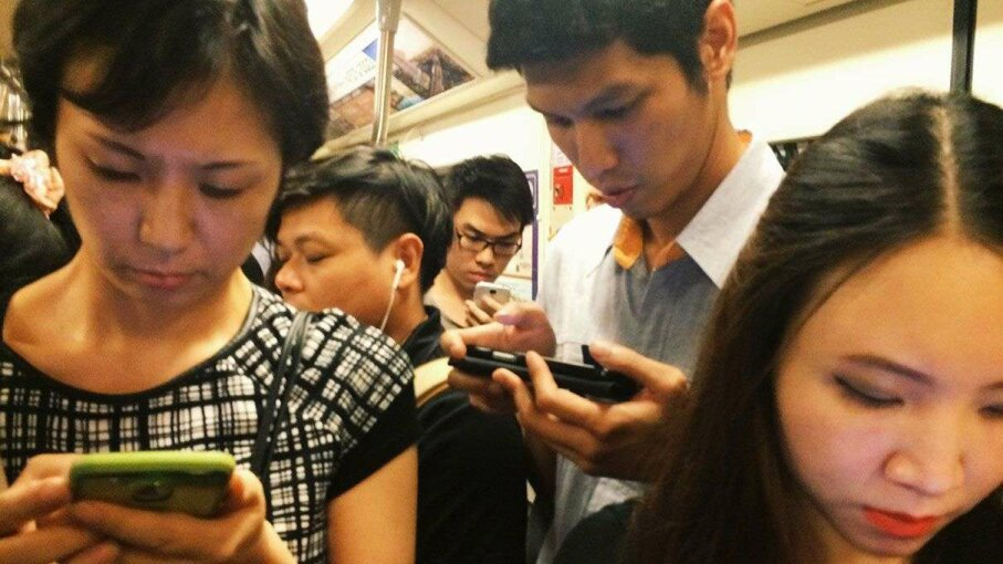 Commuters in Bangkok check their phones. Why are some people more addicted to using their smartphones than others? Natthawat Jamnapa/Getty Images