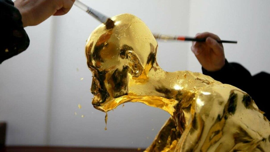 Workers apply gold leaf to the mummy of the Buddhist monk Fu Hou. Photoshot