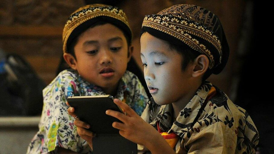 Two Indonesian children look at a smartphone. A new study suggests children may have more innovative ideas about technology than adults. Robertus Pudyanto/Getty Images