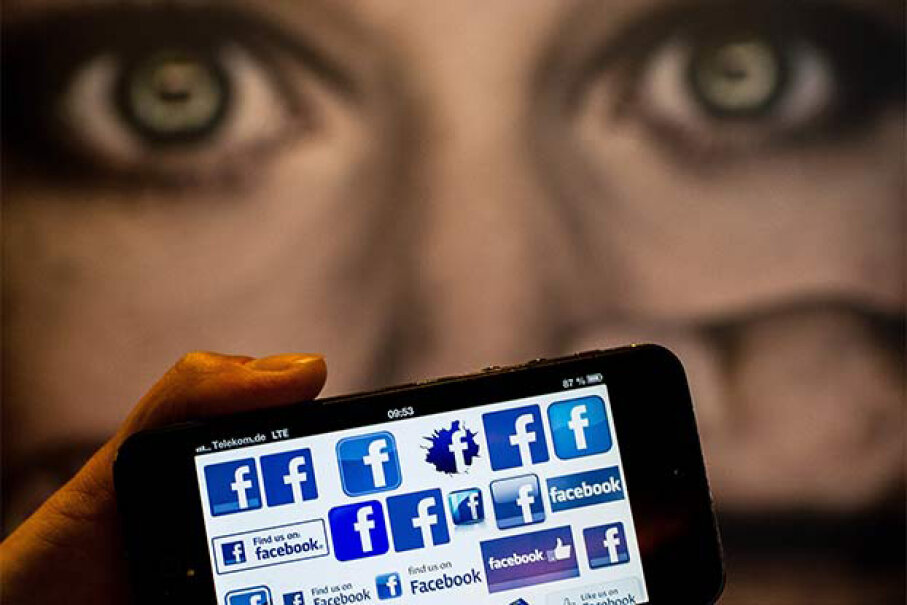 A man holds a smartphone displaying Facebook logo in front of a poster at the International Cyberbullying Congress in Berlin, Germany, in 2013. © Hannibal Hanschke/dpa/Corbis